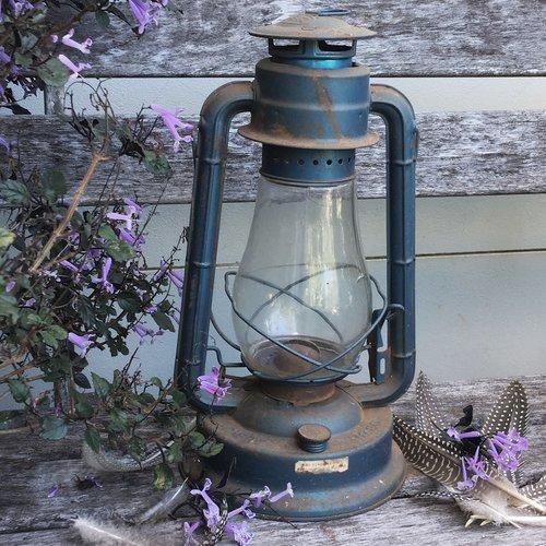 lanterna rústica e penas usadas como adereço fotográfico