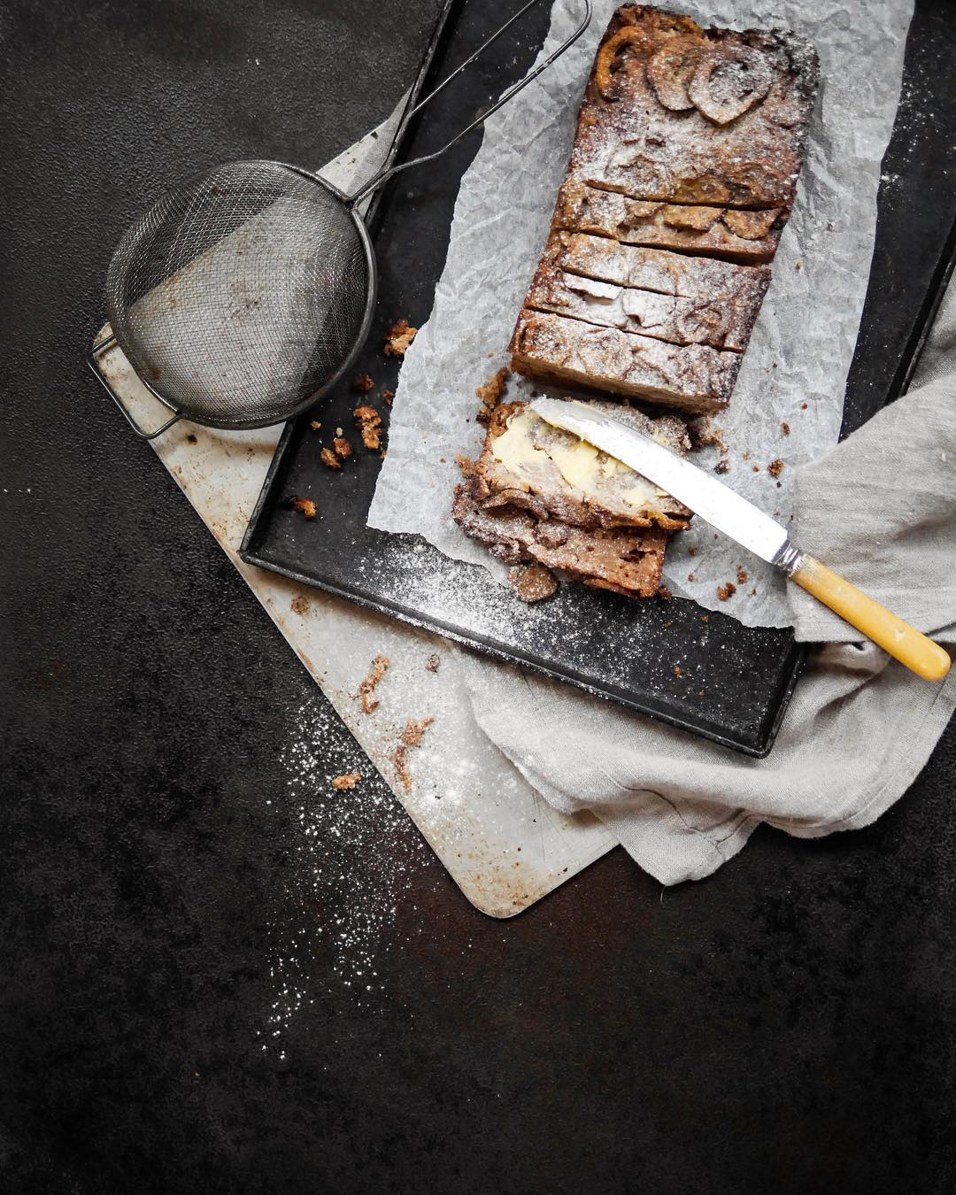 fresh baked banana bread on tray with knife and sieve