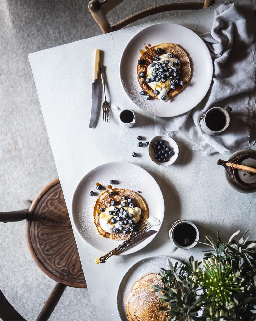 table set with plates of blueberry pancakes