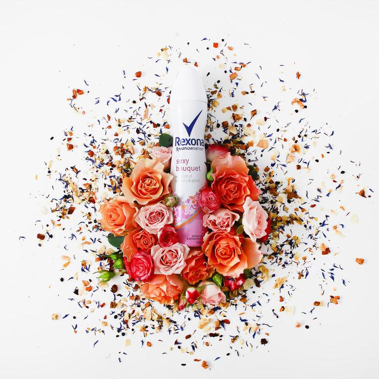 lata de desodorante cercada por rosas espalhadas e pétalas secas
