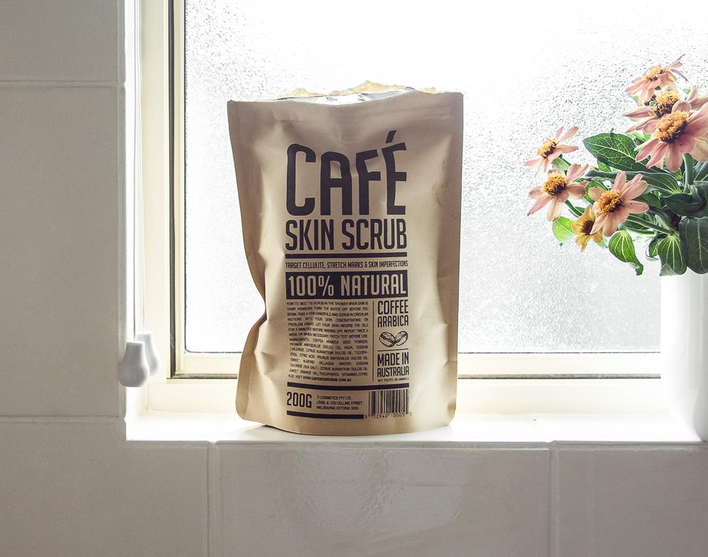 Esfoliante de café no peitoril da janela com vaso de flores