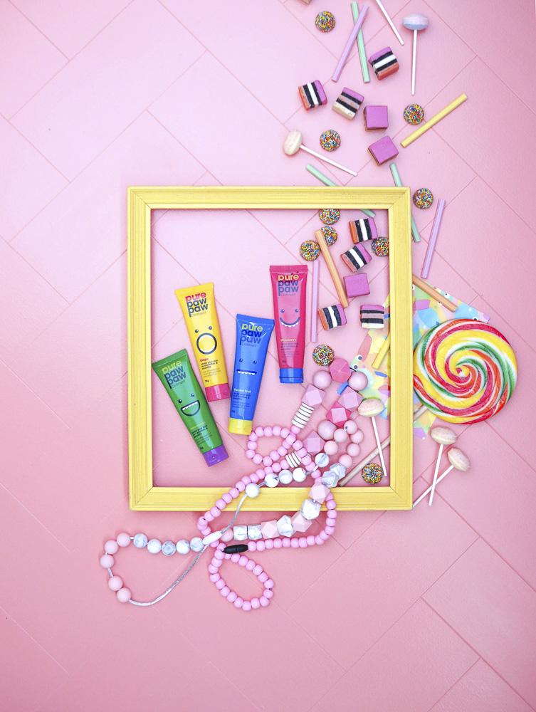 Moldura amarela com tubos e doces em um fundo de mosaico rosa