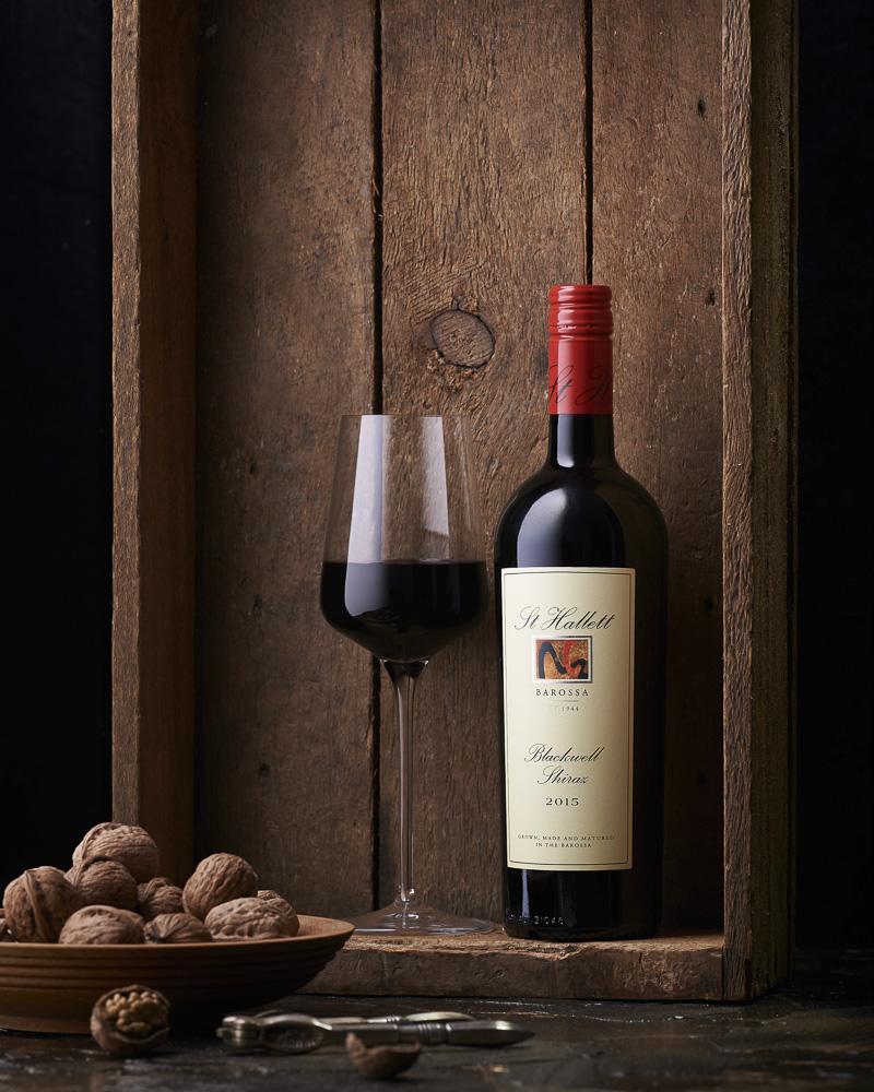 Garrafa de vinho e taça de vinho tinto com nozes em uma caixa de madeira