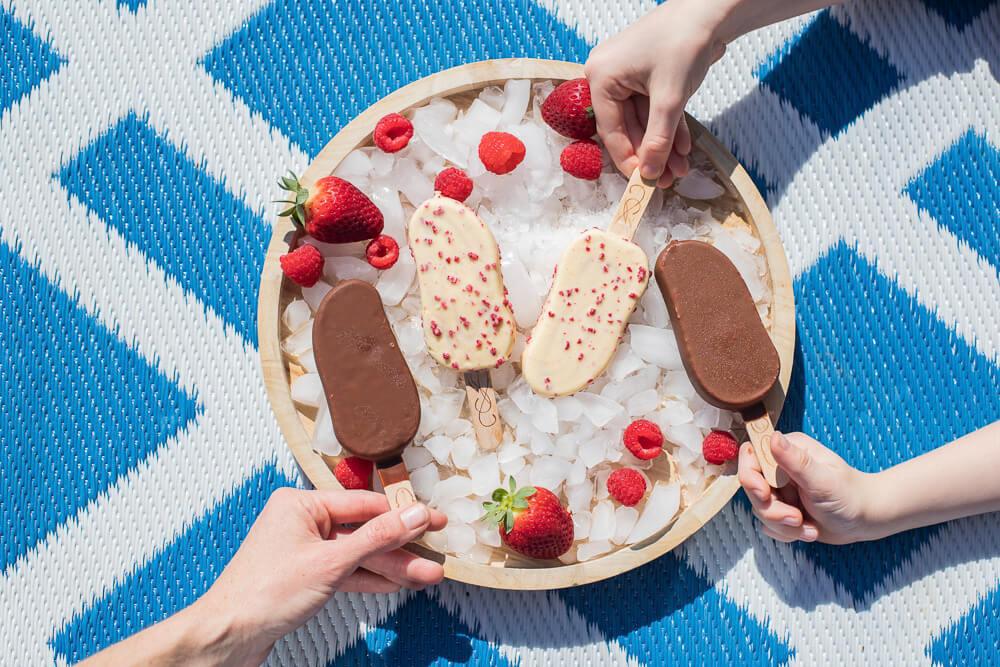 Bandeja circular cheia de gelo com as mãos pegando o sorvete