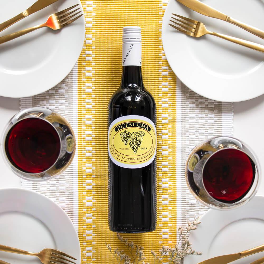 Mesa posta para o jantar com uma garrafa de vinho tinto no corredor amarelo