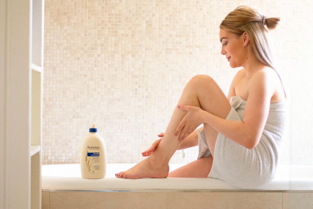 Mulher aplicando hidratante enquanto está sentada na borda da banheira