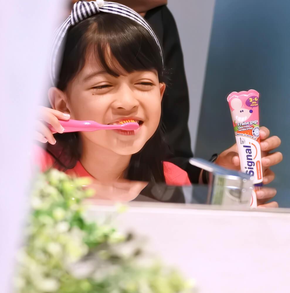 garotinha limpando os dentes com uma escova rosa segurando pasta de dente infantil