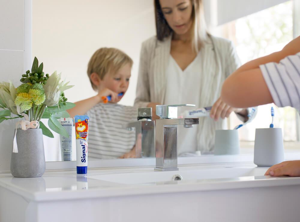Mãe e filho limpando os dentes na pia do banheiro refletidos no espelho