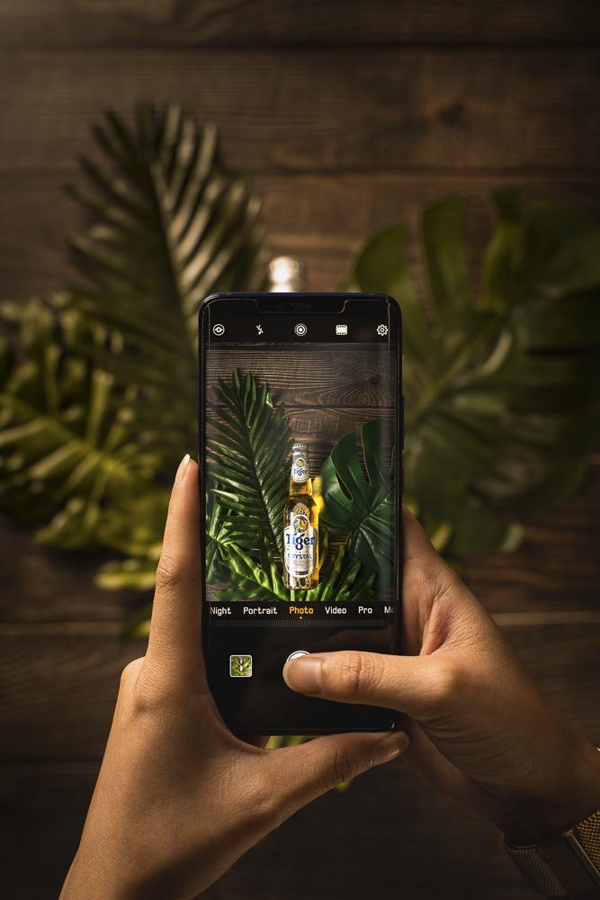 olhando pela tela de um celular para a foto de uma cerveja em folhas de palmeira