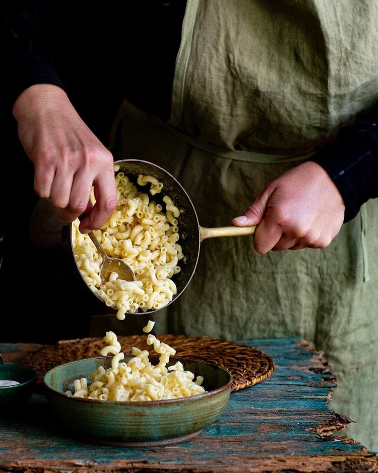 serving up macaroni into a bowl