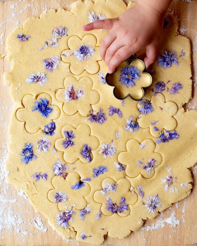 using cookie cutters on shortbread with cornflowers