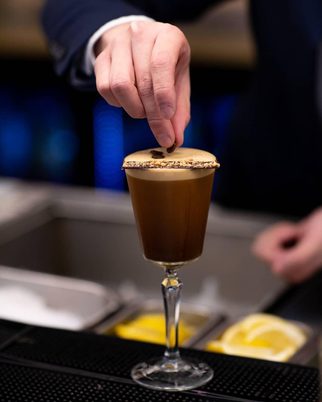 adding a coffee bean garnish onto an espresso martini