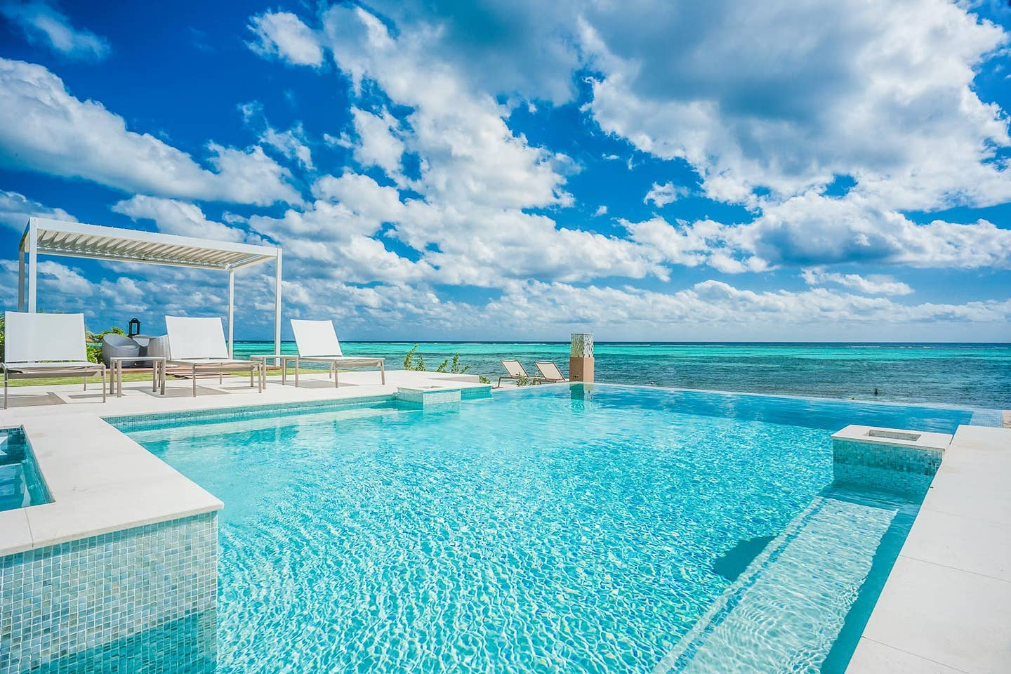 An outdoor pool overlooking a clear blue ocean