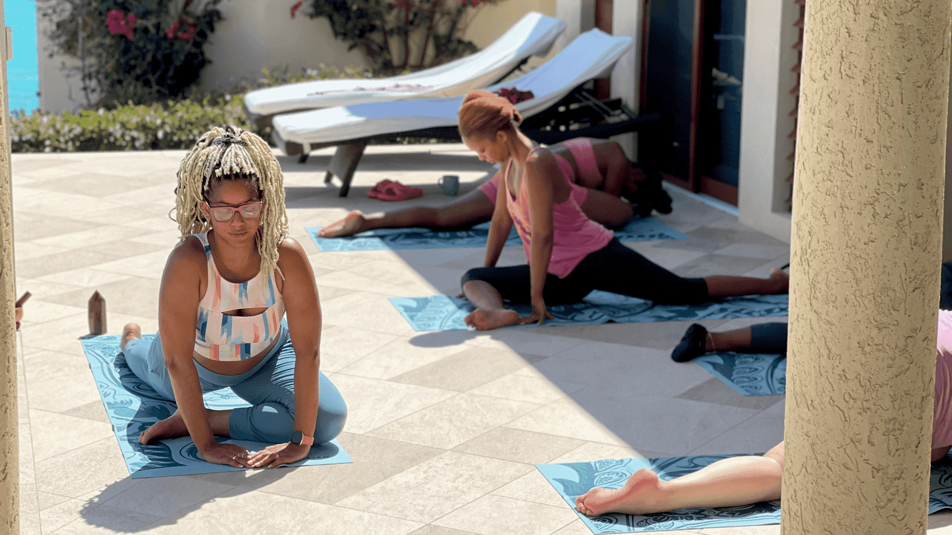 Several women doing yoga stretches outside.