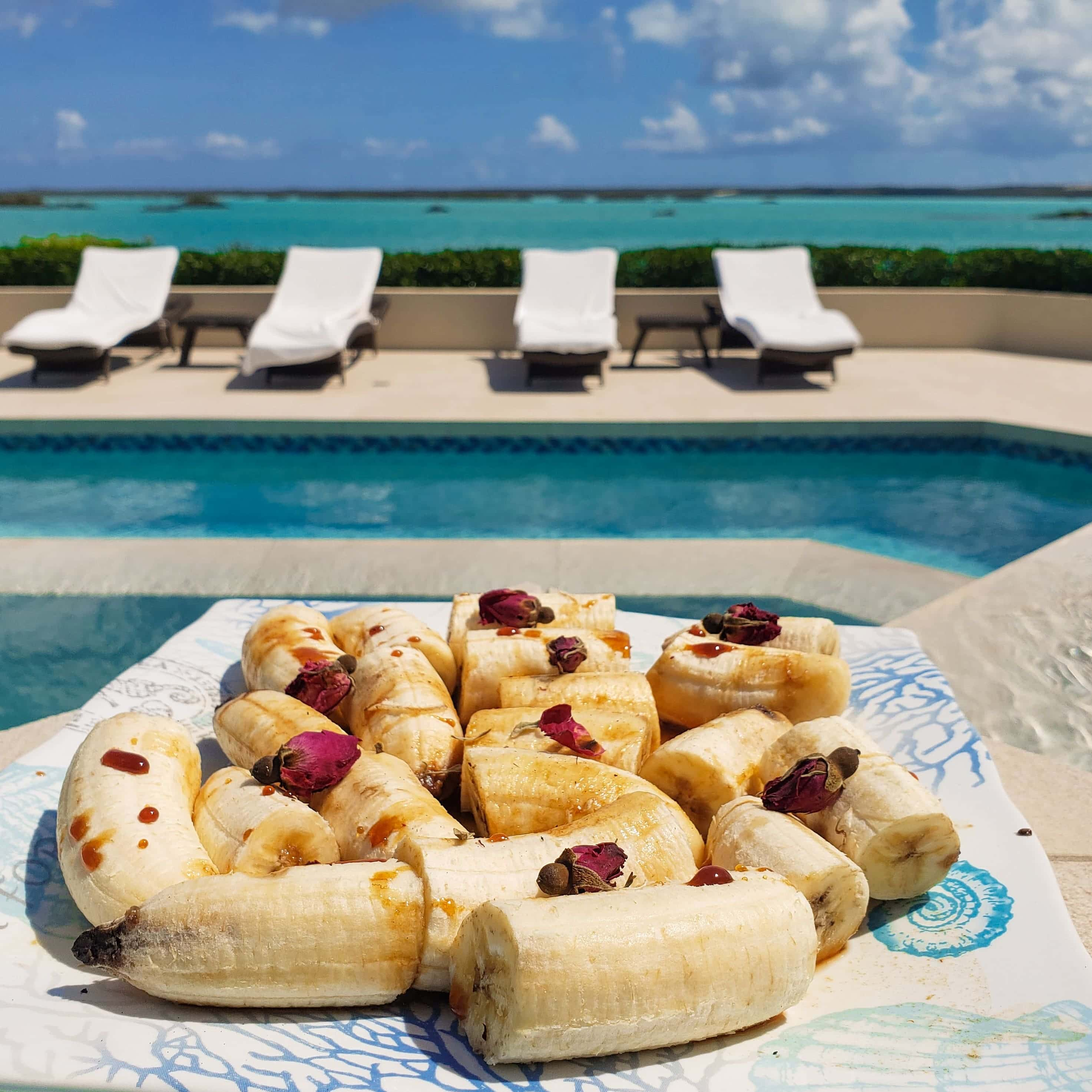A plate of a banana-based food placed near an outdoor pool overlooking the ocean.