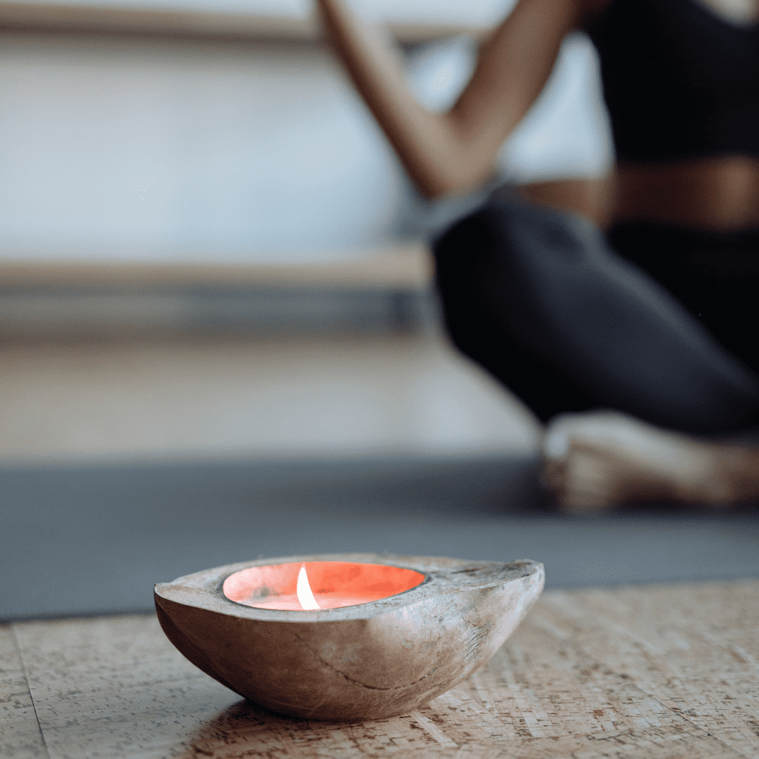 A lit candle with a woman meditating in the background
