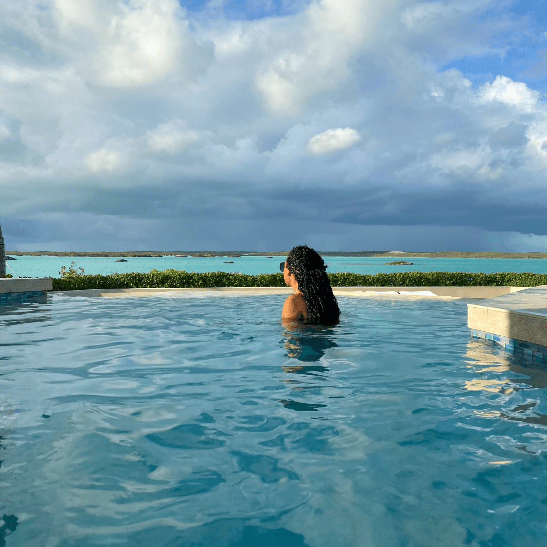 A woman in a pool overlooking a clear blue ocean