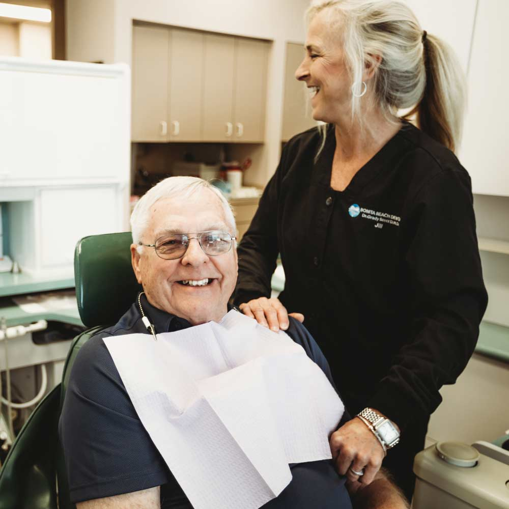 Photo of a patient in a dental chair with a team member standing beside him