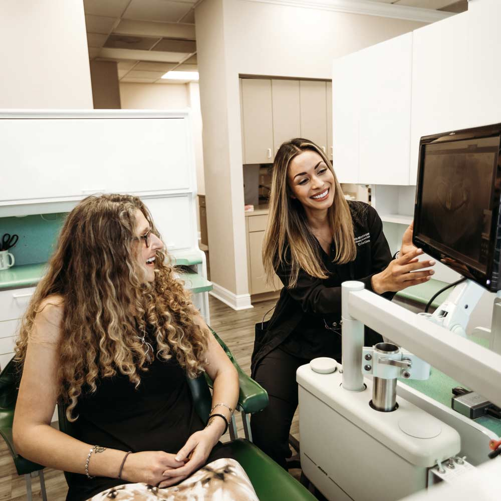 Photo of a team member showing a patient a digital x-ray scan on a monitor