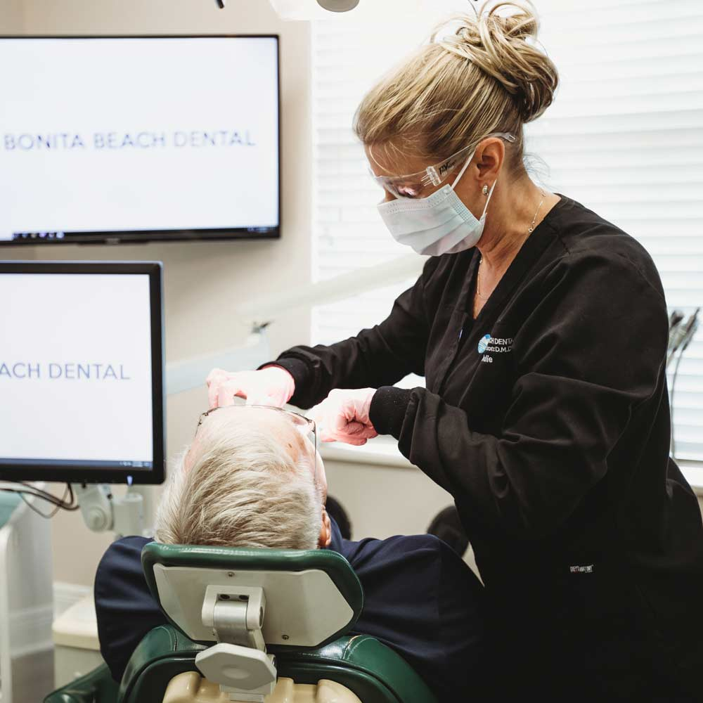 Photo of a team member looking at a patient's teeth