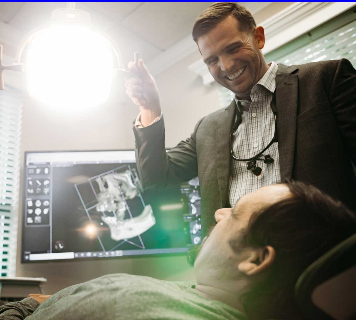 Photo of Dr. Scott smiling at a patient with a 3D x-ray scan in the background