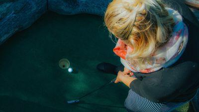 Fotografie s ženou hrající golf na místním putting golfovém hřiši.