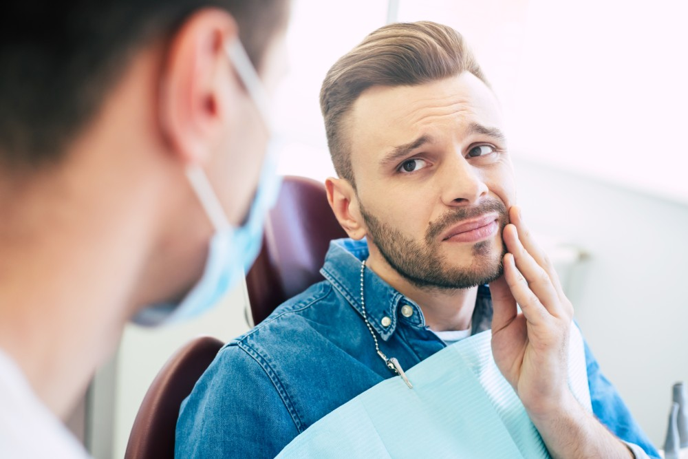 man holding mouth in pain in dental chair
