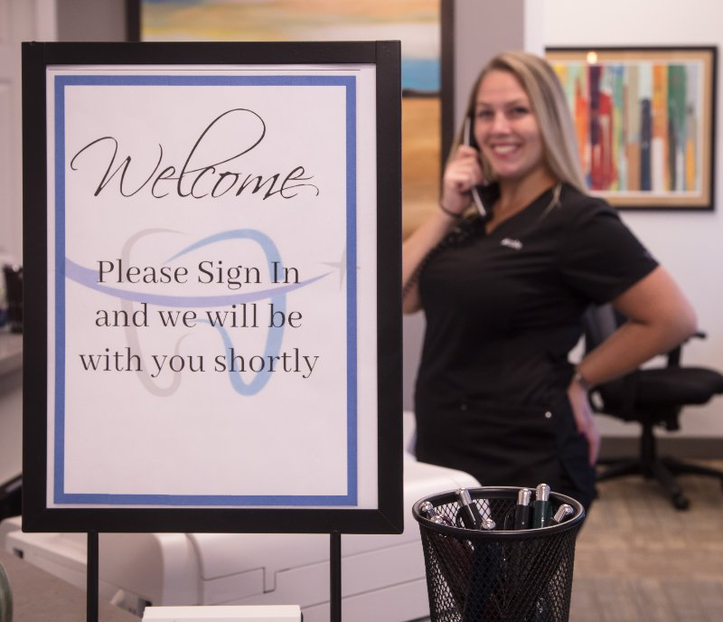 staff member smiling on phone in front of welcome sign
