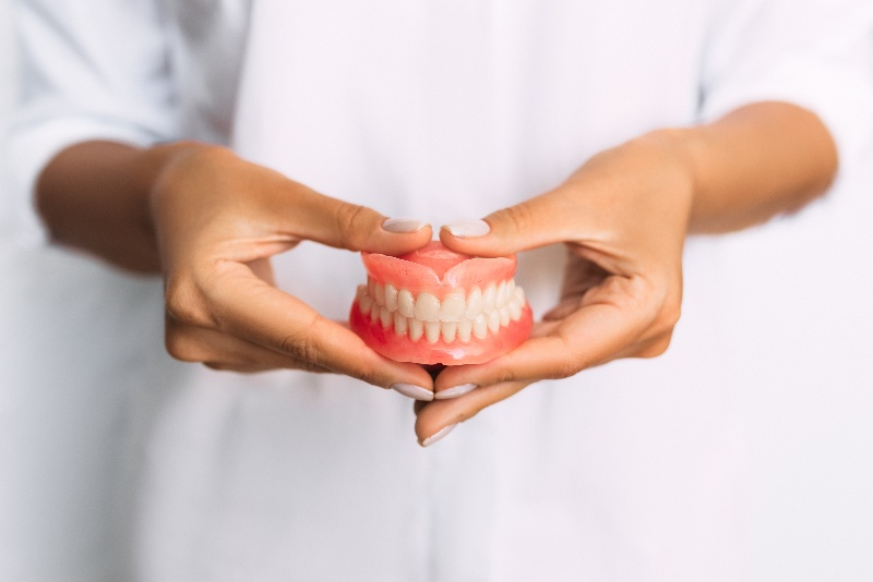 person in white holding dentures