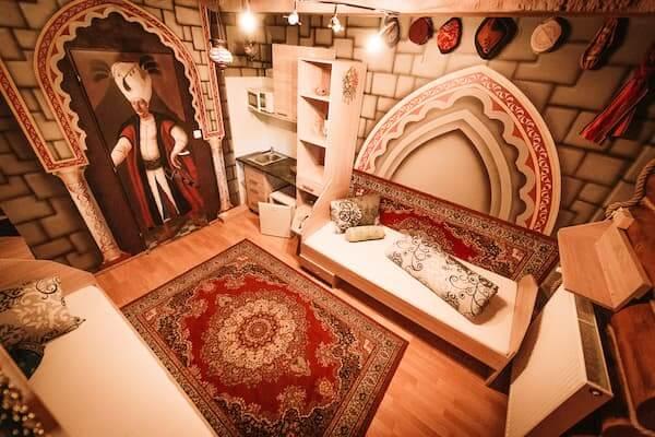 Převládá modrá barva, stropy z kobercoviny, koberce na zdech. Turecké lampy a dekorace. V koupelně mozaika muslimské mešity s dvěma minarety, dvě oddělené postele, vyřezávaná skříň a stůl.