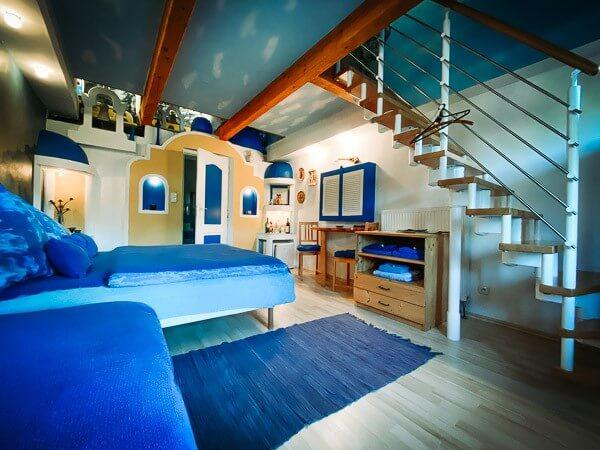 Převládá tmavě modrá barva, v interiéru se budete cítit jako na pláži, na zdi malovaný západ slunce, tlumené světlo ve stavbičkách na jednom s řeckých ostrovů. Klimatizovaný pokoj s manželskou postelí.