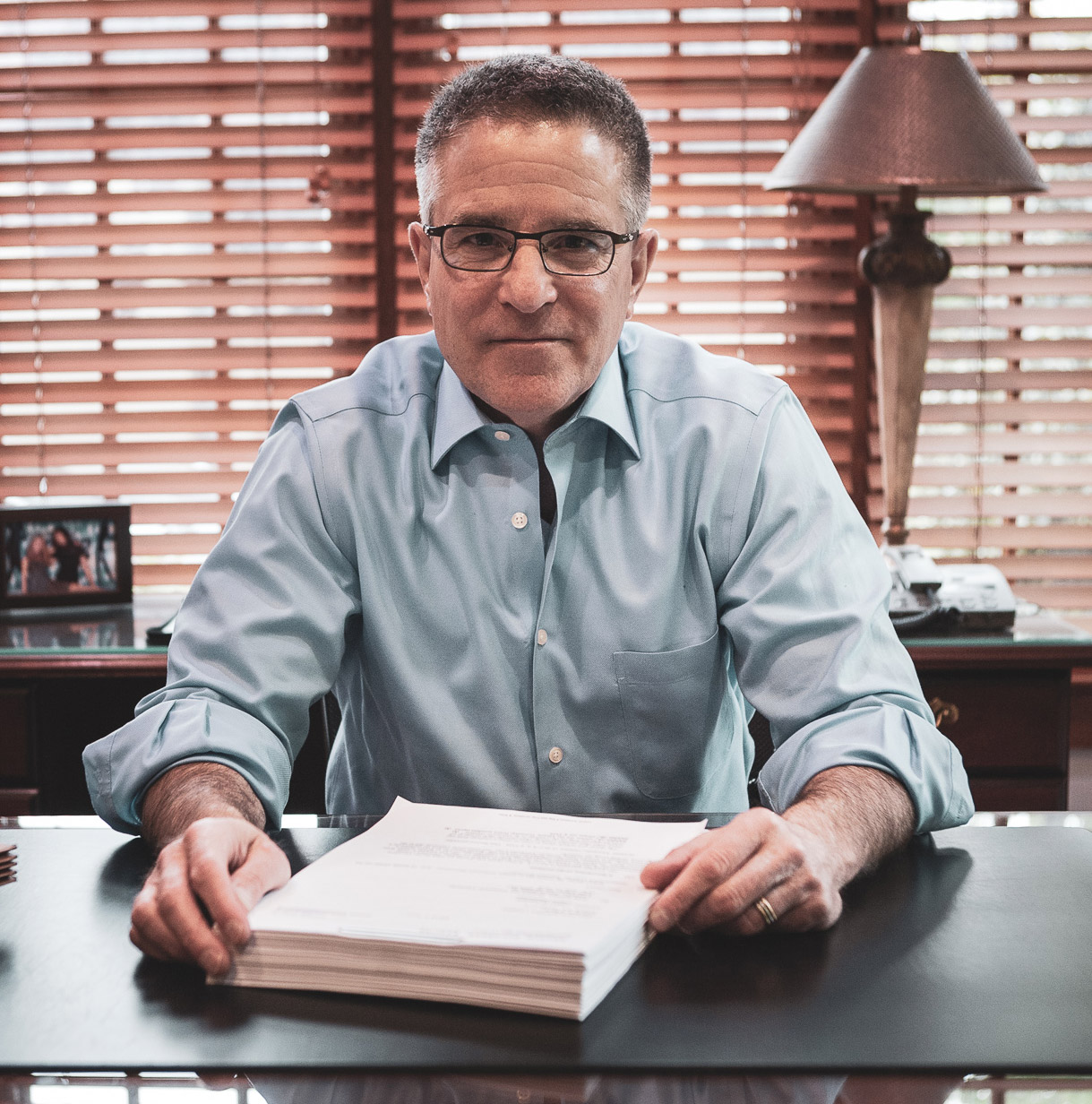 Andrew Goldberg sits in front of a stack of case materials.