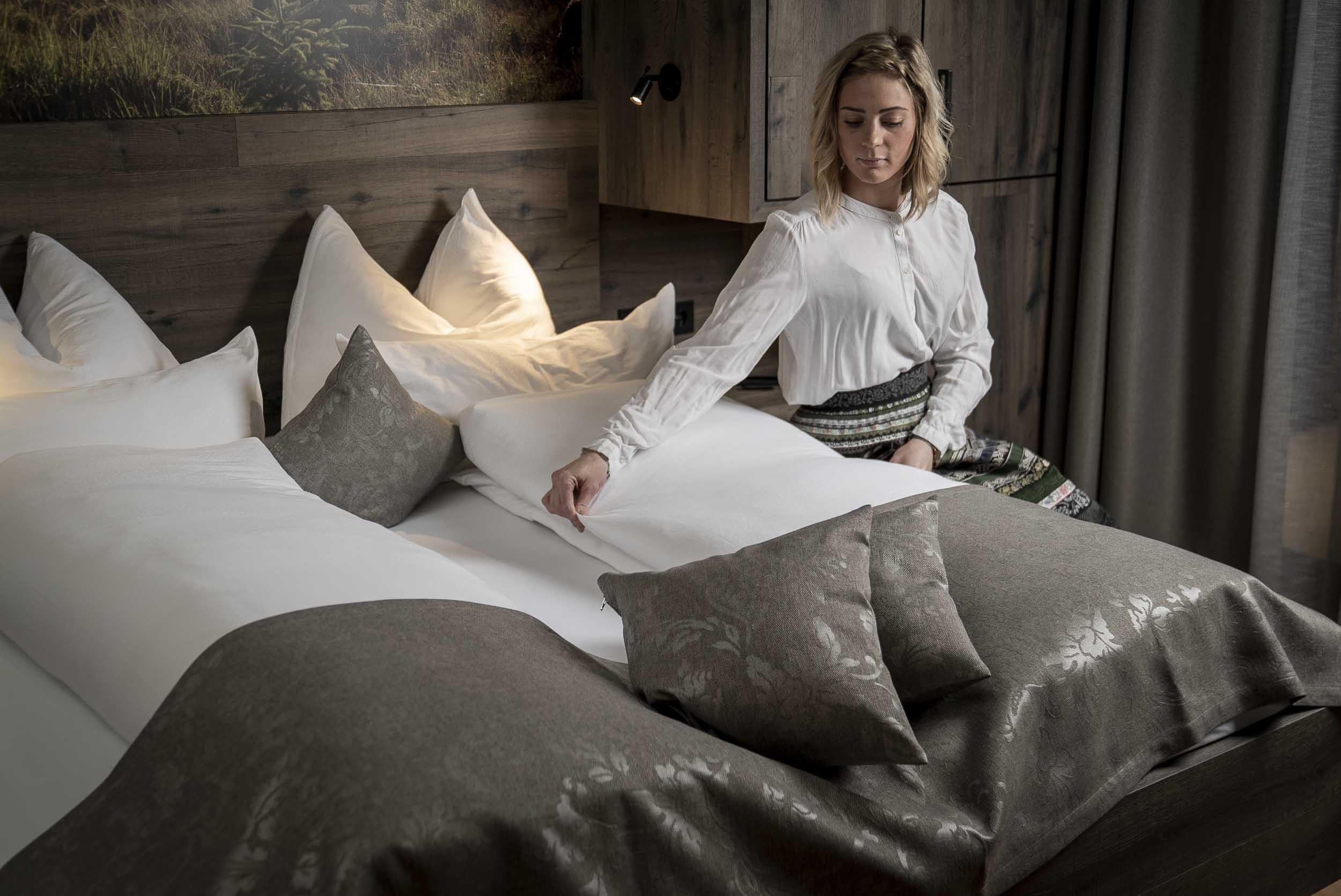 Anna streicht die Bettdecke glatt.