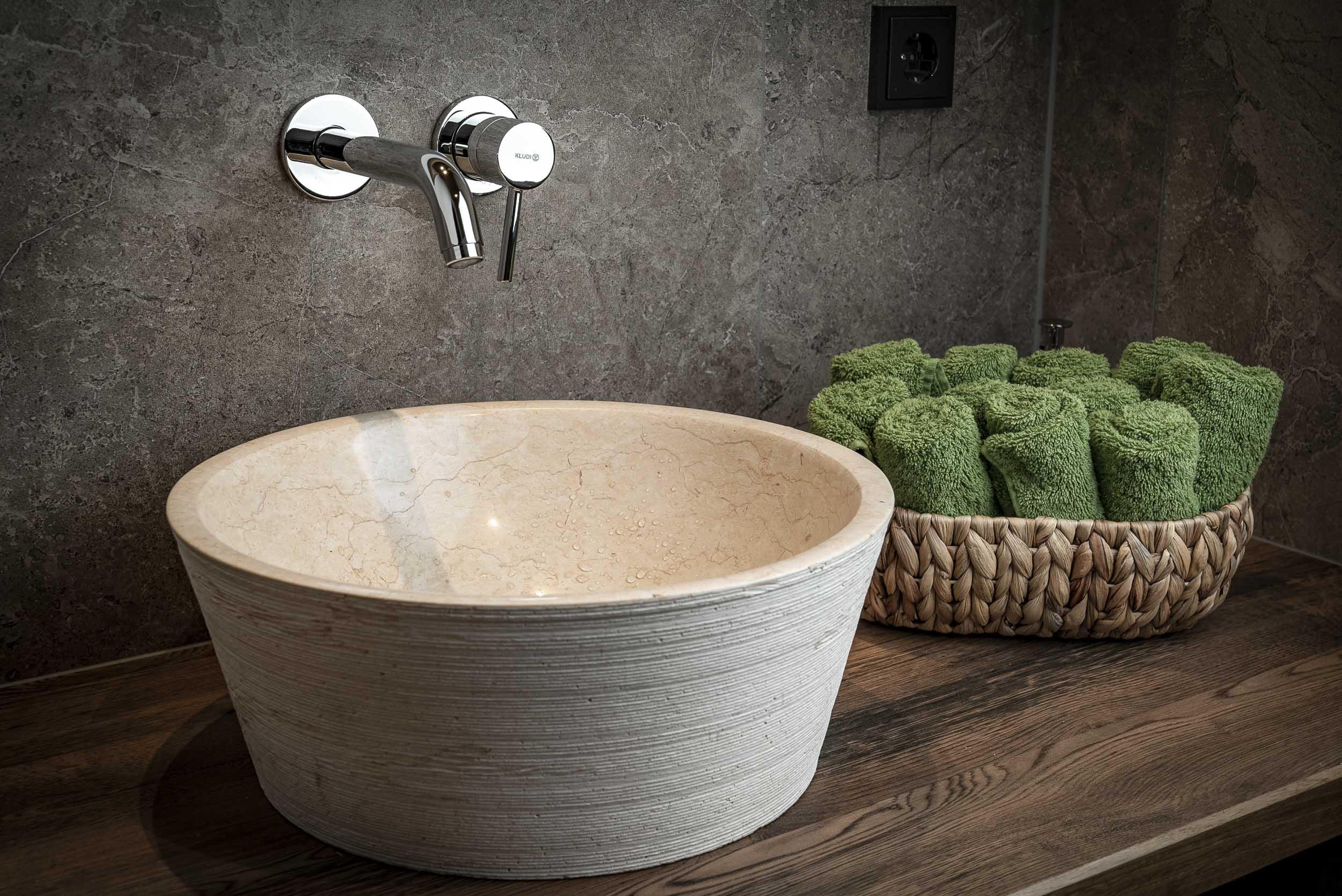 Waschbecken und Handtücher in Annas Saunabereich.