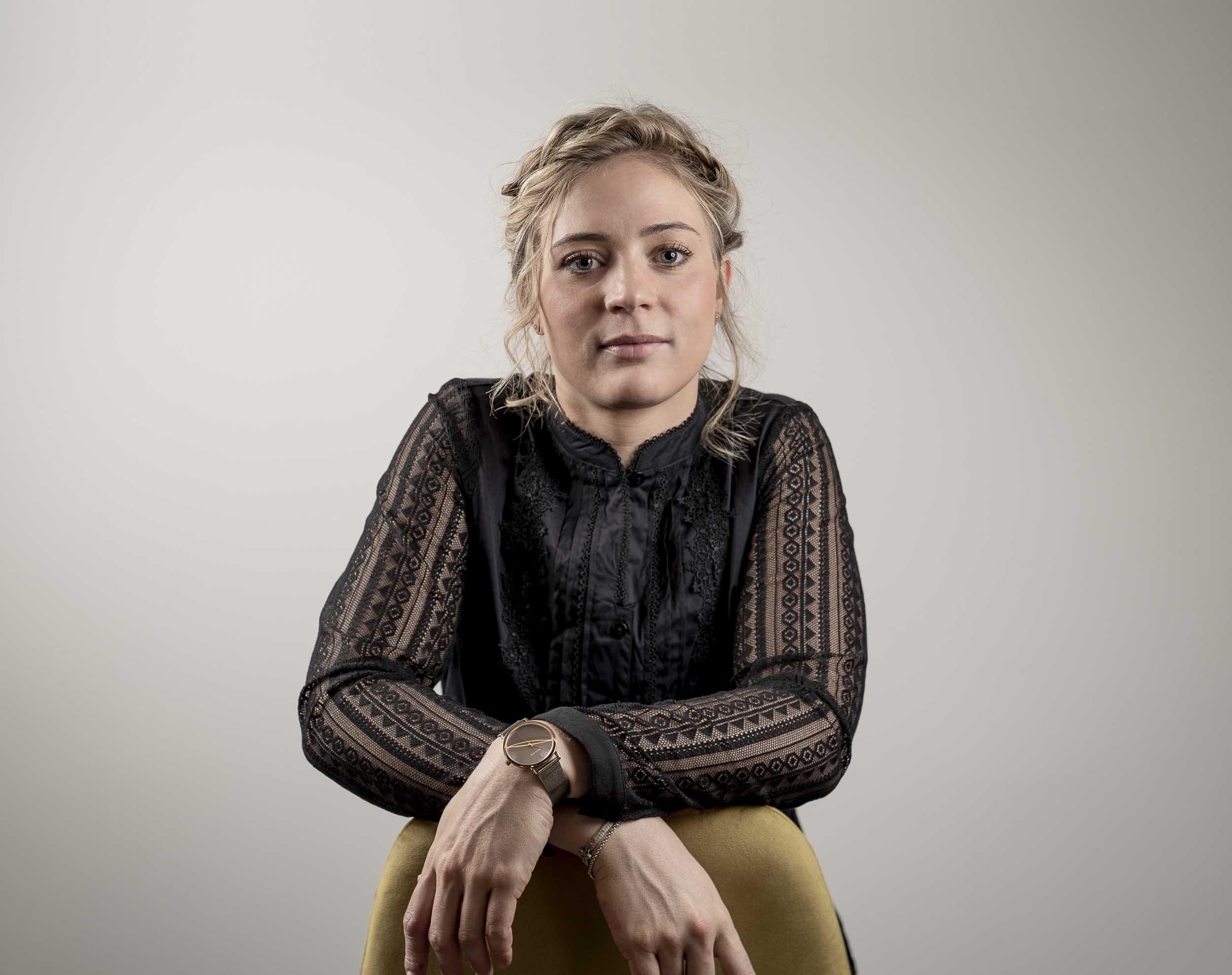 Anna-Katharina Feyersinger sitzt auf einem Stuhl und verschränkt ihre Hände.