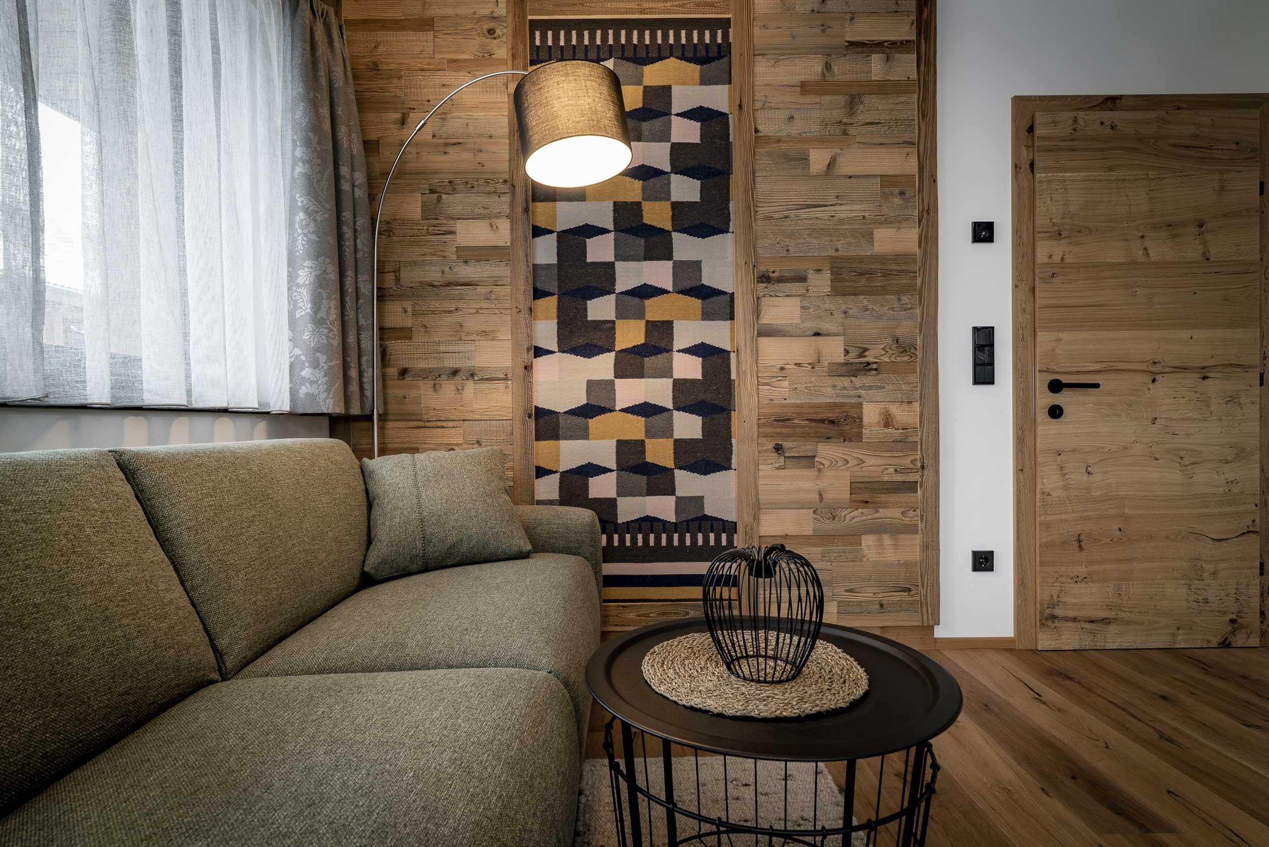 Wohnbereich mit Couch, Couchtisch und designter Holzwand.