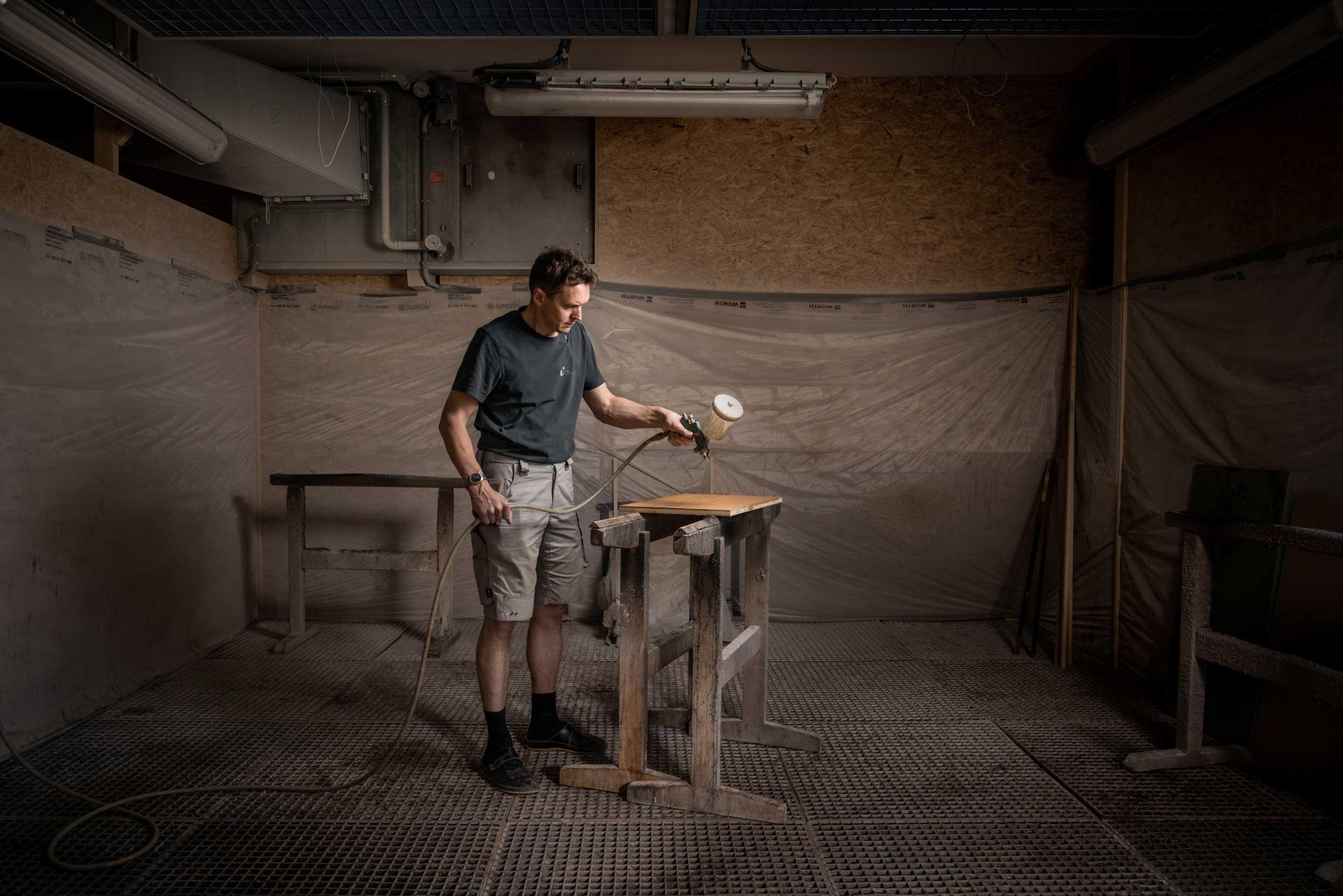 Alexander Feyersinger behandelt ein Holzelement mit Öl.
