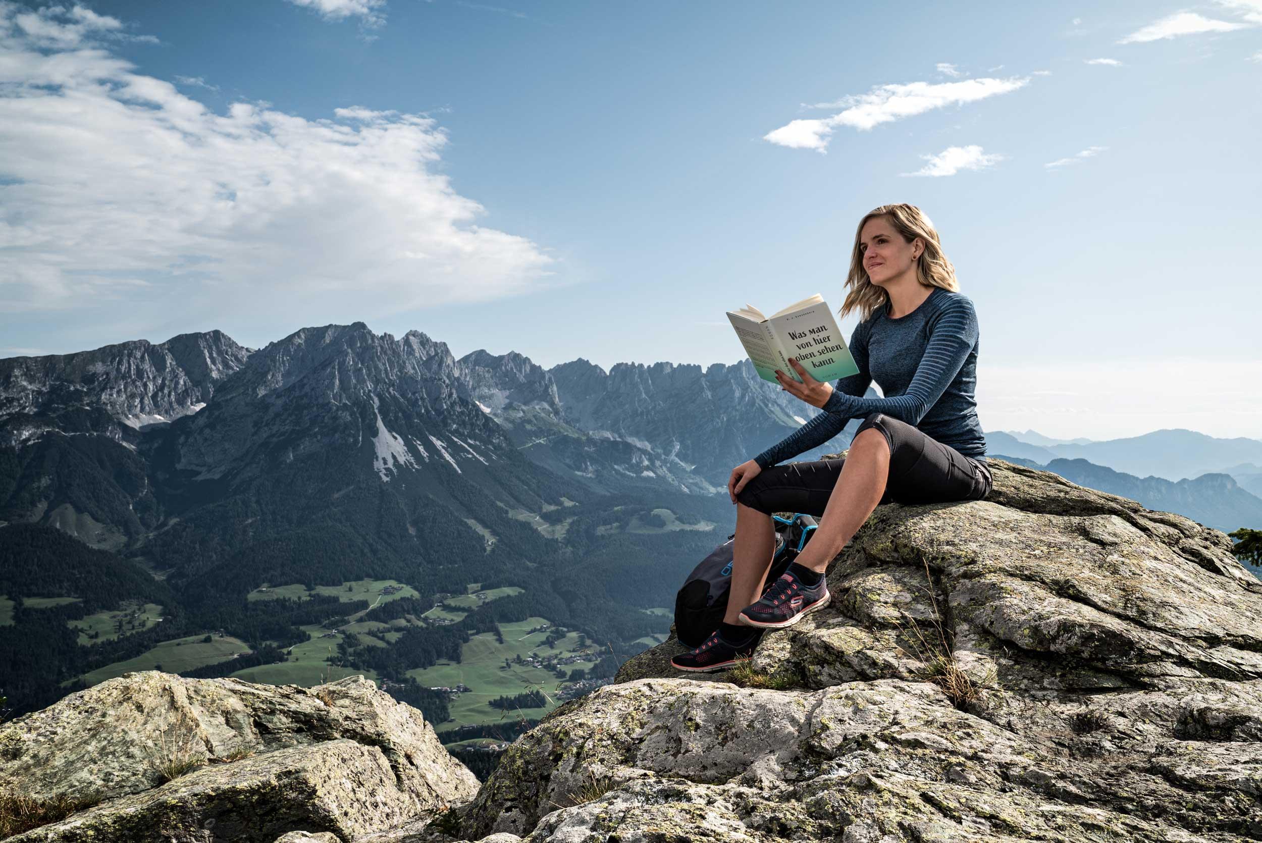Wanderin sitzt auf einem Felsen und liest in einem Buch.