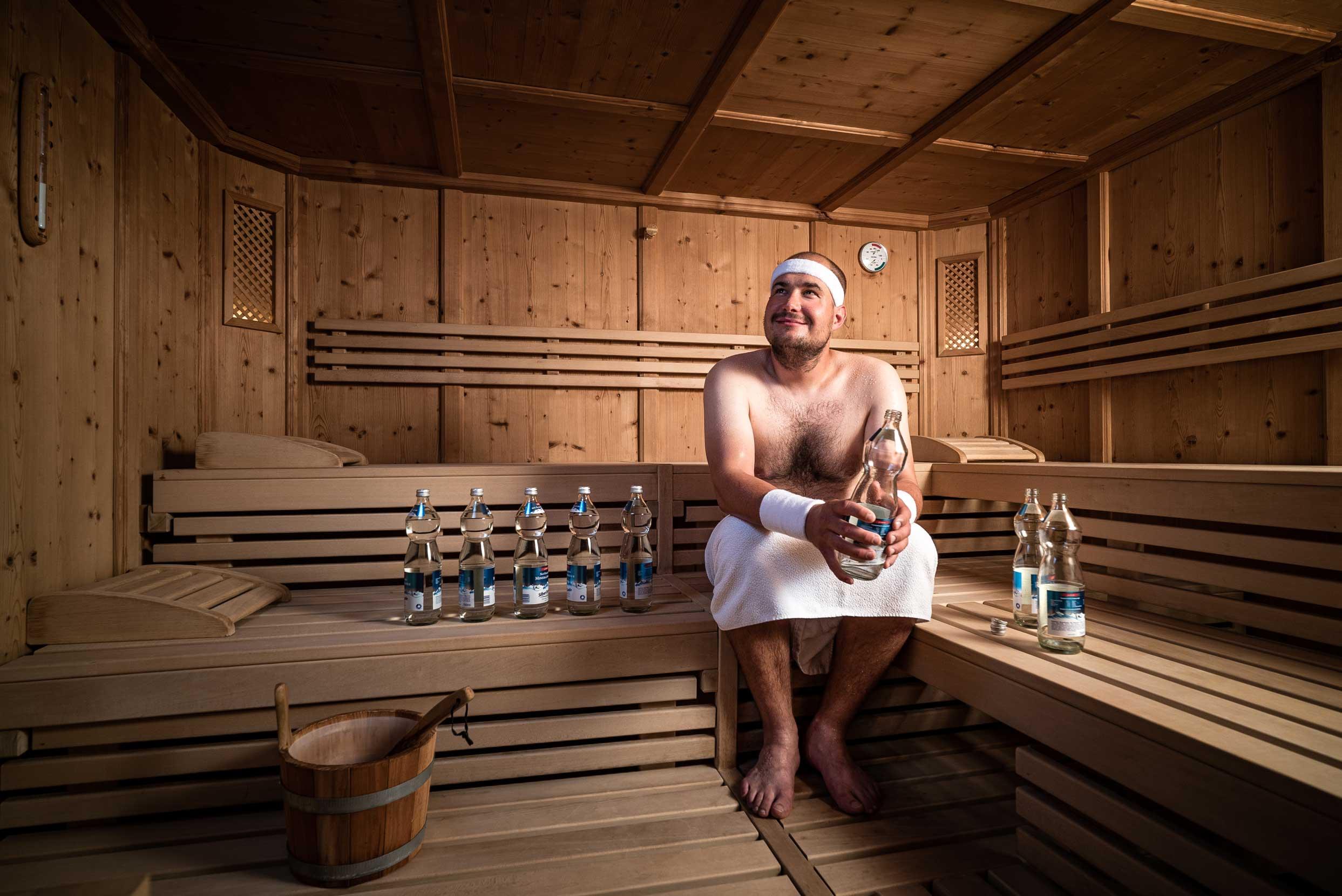 Gast sitzt mit vielen Mineralwasserflaschen in Sauna.