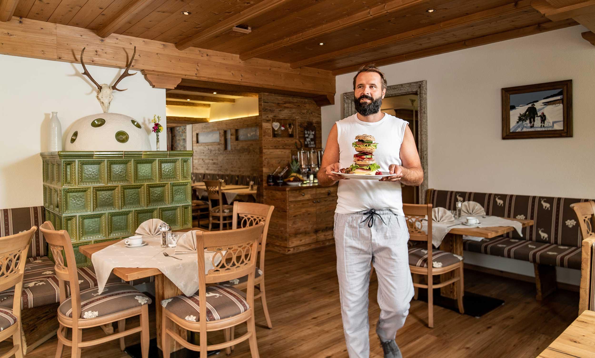 Gast schreitet mit einem riesigen Frühstücks-Burger zu seinem Tisch.