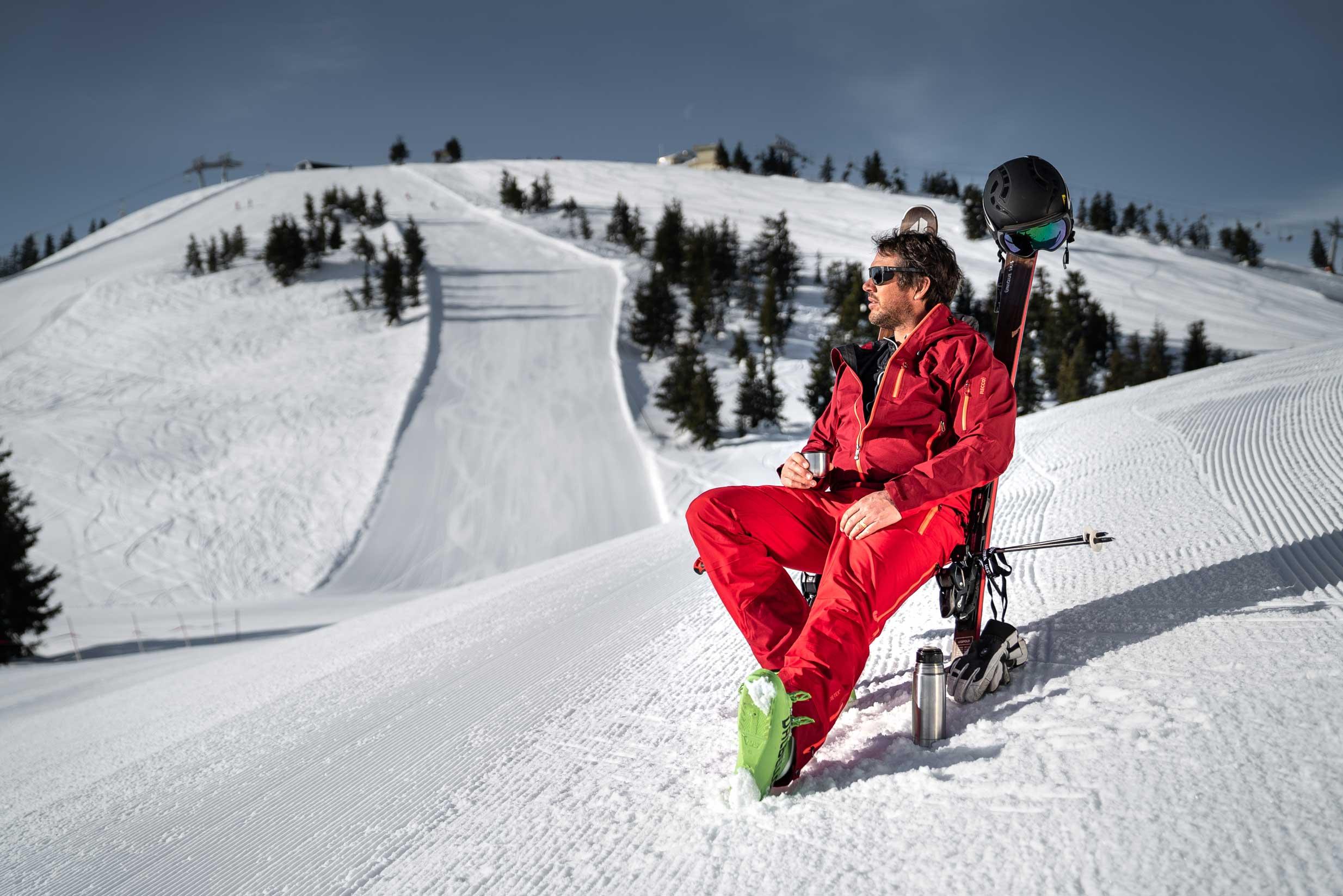 Skifahrer sitzt aus selbst gemachtem Stuhl auf der Piste und genießt die Ruhe und den Ausblick.