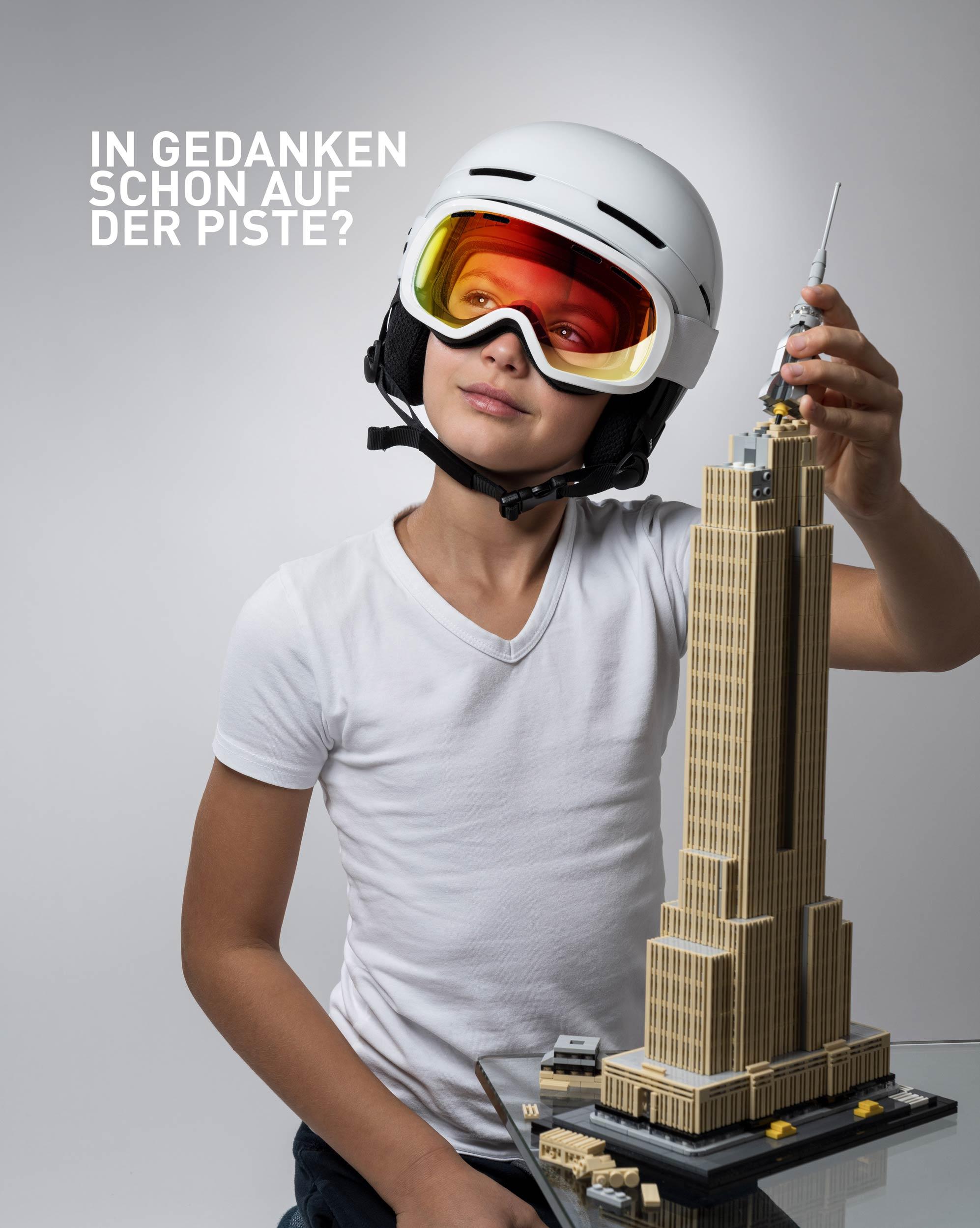 Kampagnensujet Winterstart mit einem Jungen beim Legospielen.