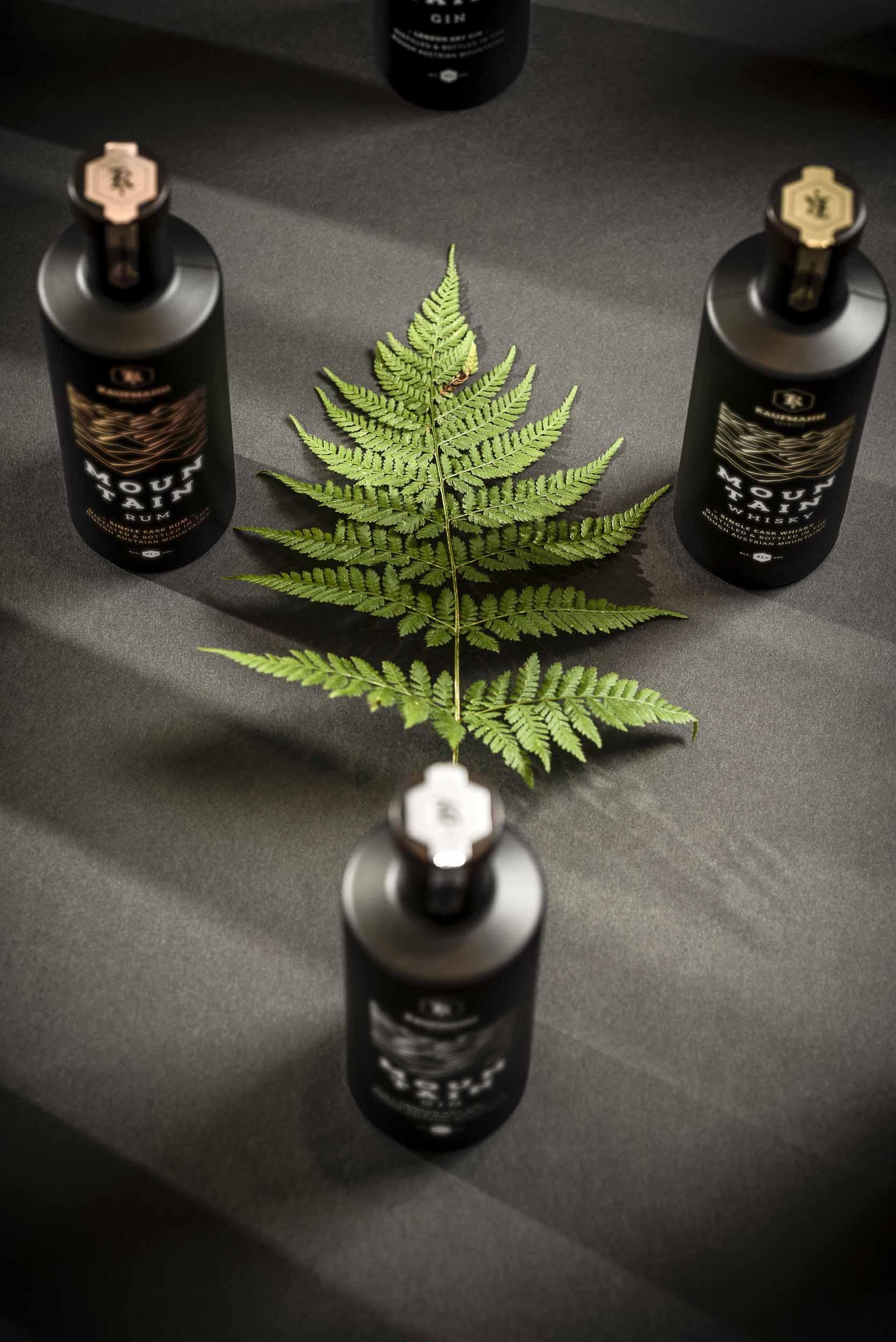 Mountain Gin, Mountain Rum, Mountain Whisky und ein Farnblatt.