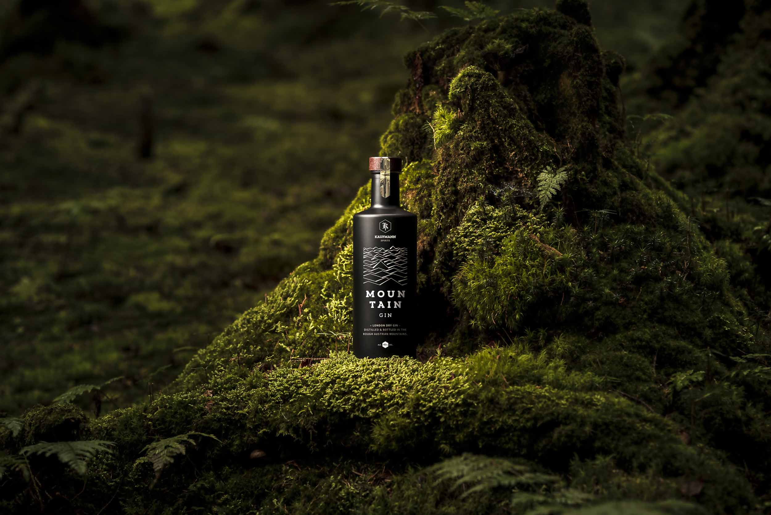 Ein Flasche Mountain Gin vor einem vermoosten Baumstumpf im Wald.