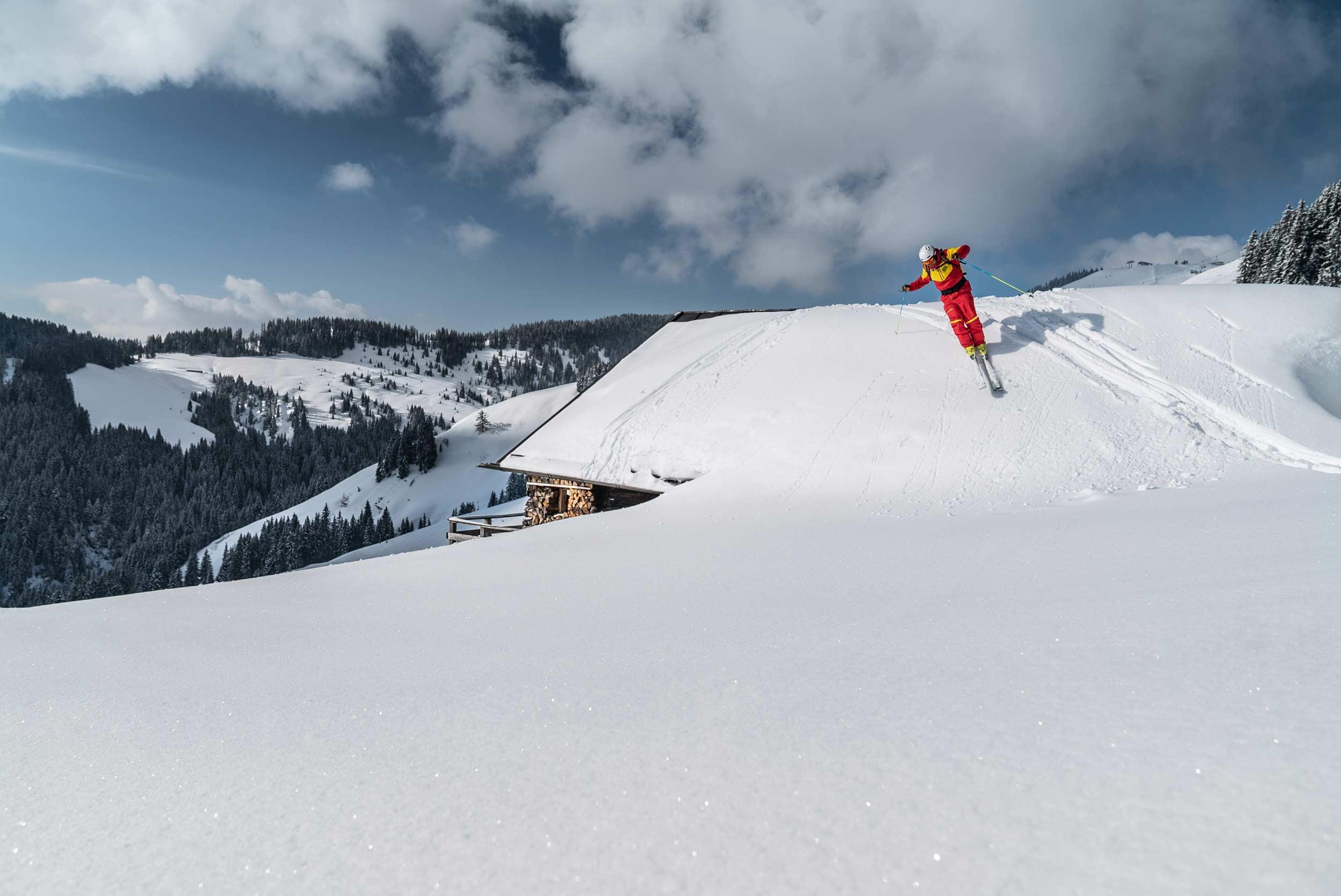 Ein Skilehrer der Top Skischule Ellmau schwingt von einem verschneiten Almdach.