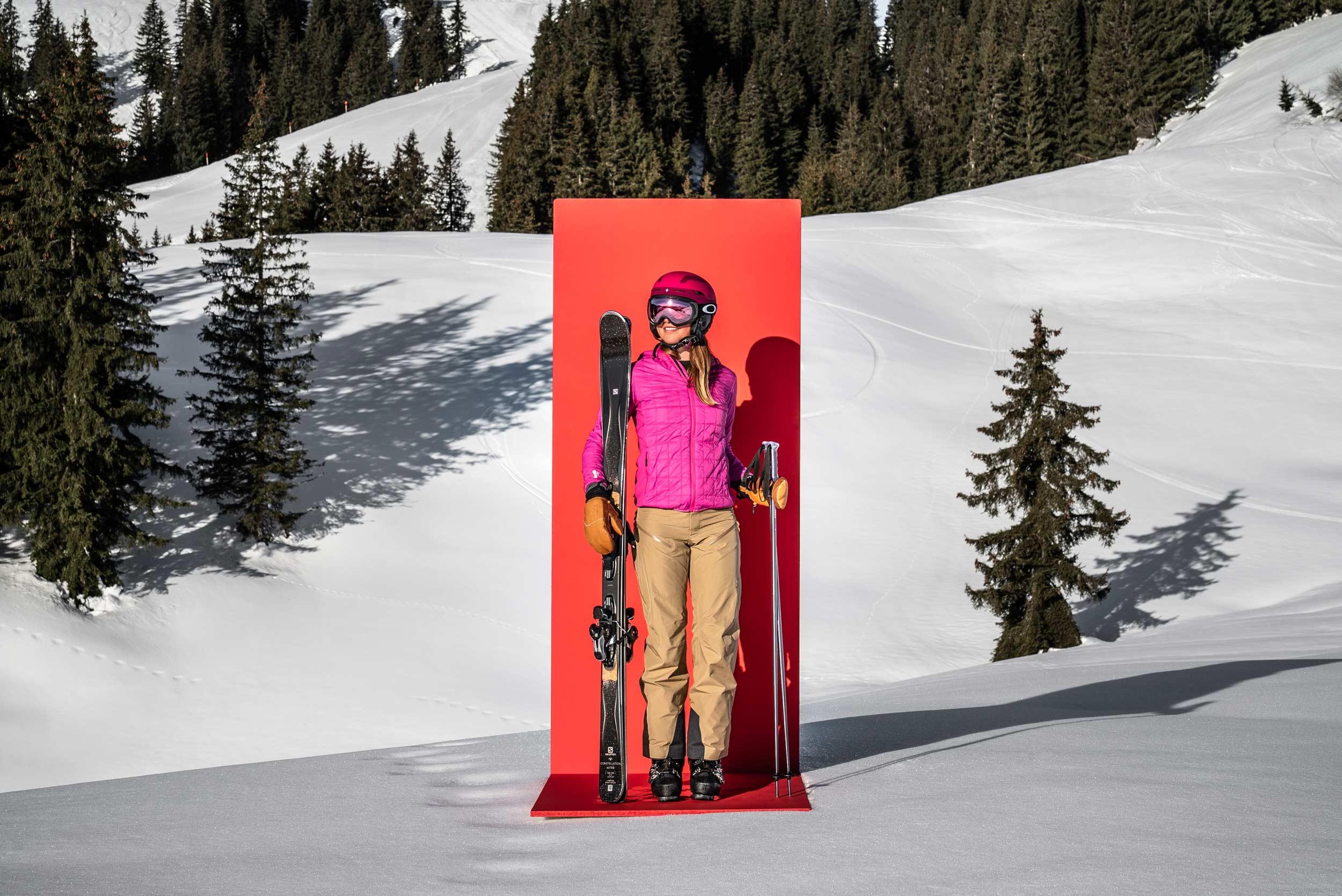 Eine Frau posiert stolz vor einer roten Tafel.