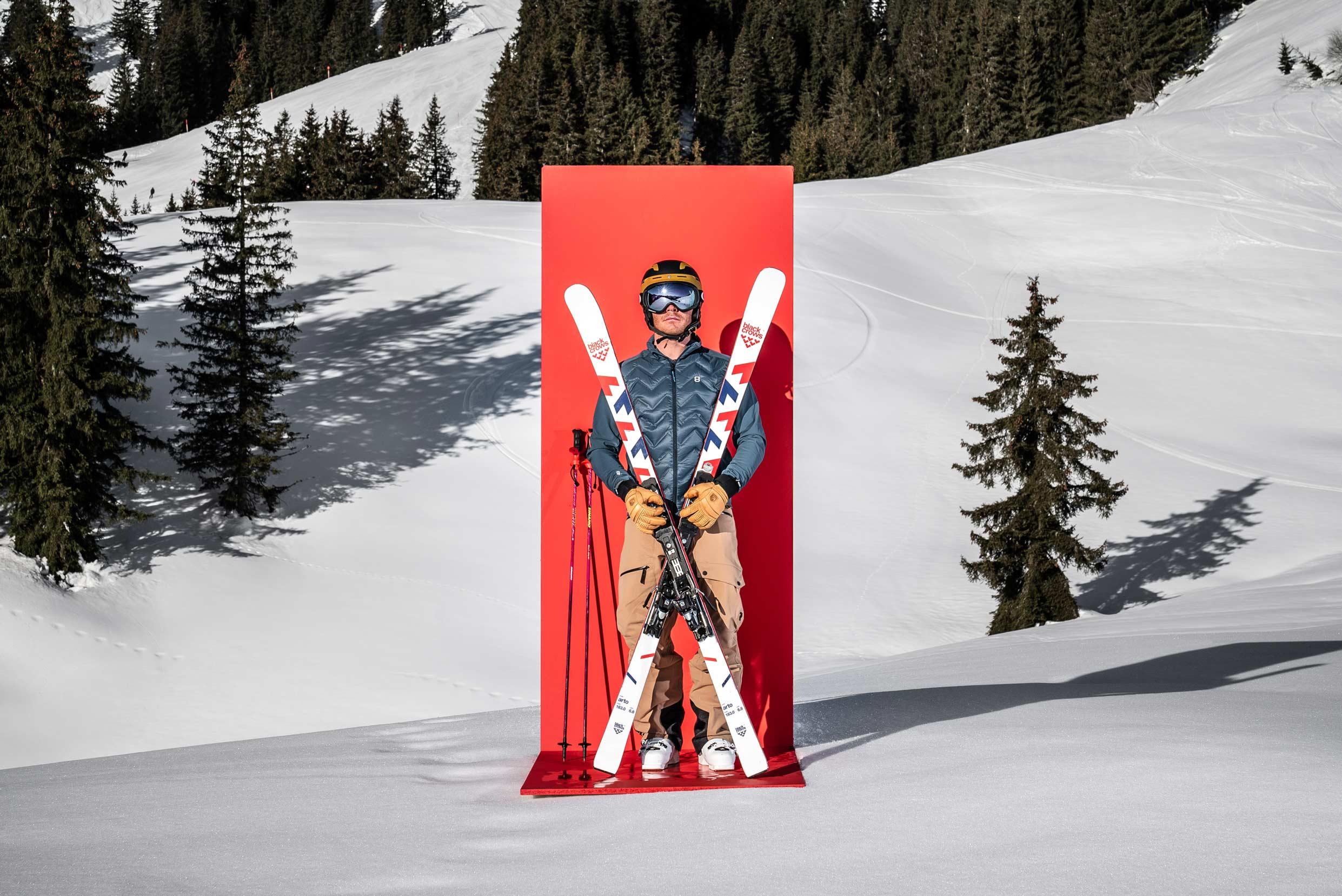 Ein Mann posiert stolz im Skigebiet vor einer roten Tafel.