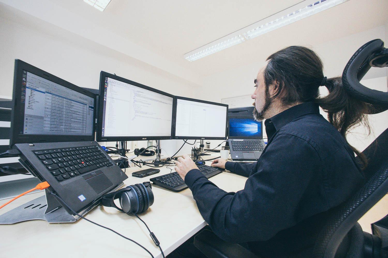 Software Entwickler im mittleren Alter arbeitet in einem modernen Büro am Computer.