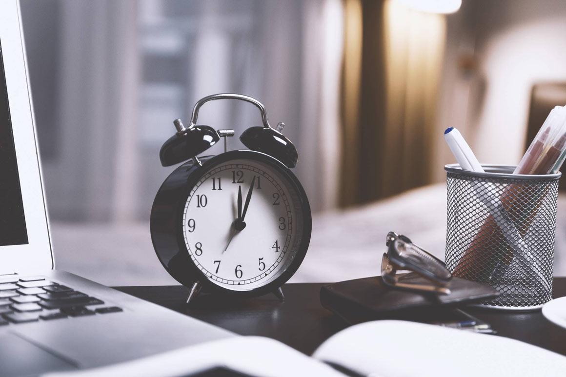 A black alarm clock on an office desk.