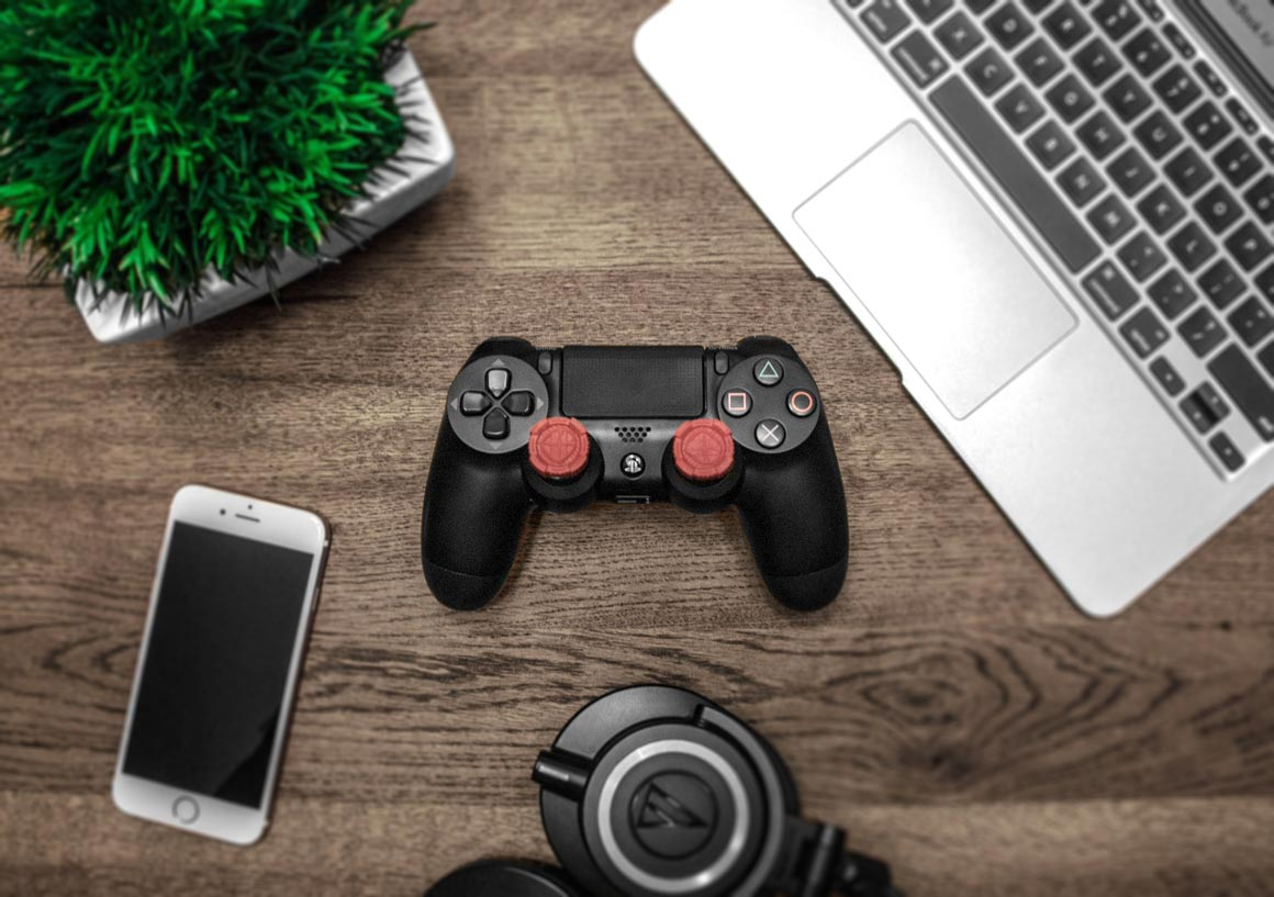 A playstation controller, iPhone, MacBook on a wooden table.